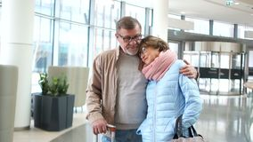 Travel impressions. A man and a middle-aged woman at the airport are waiting for their flight. The beginning of a stock footage