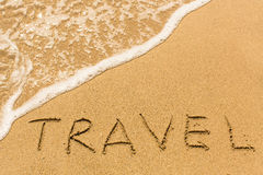 Travel - inscription by hand on yellow beach sand. Happy. Stock Images