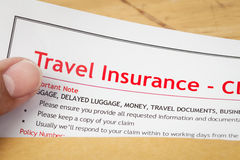 Travel Insurance Claim application form and human hand on brown Royalty Free Stock Image
