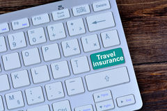 Travel insurance on keyboard button Stock Photography