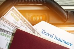 Travel Insurance tag on suitcase near numeric combination lock,p. Assport and US Dollar. Travel Insurance is intended cover medical expenses,cover lost luggage Stock Photos