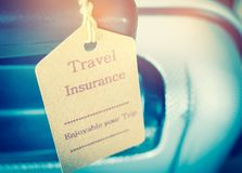Travel Insurance tag on Suitcase safety with letters enjoyable y. Our trip on bag light blurred background, that is intended cover medical expenses, trip Stock Photography