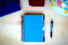 Travel items, blue notepad, pen, pc, globe on wooden background Stock Photography