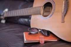 Travel journal with acoustic guitar. Travelling with guitar, journal and sunnies Stock Image