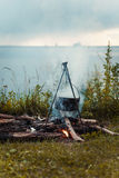 Travel a kettle over a fire burning on the river and sunset backgroun.Cooking over a campfire Stock Photos