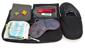 Travel Kit: map, earplugs, eye band for sleeping, socks, inflata. Ble pillow, toothbrush and toothpaste. Set closes in black fabric sachet . The composition Stock Photography