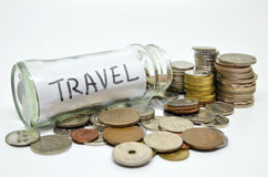 Travel lable in a glass jar with coins spilling out Royalty Free Stock Images