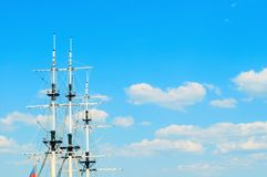 Travel landscape - ship masts with rigging on the background of the blue summer sky. Concept of sea travel. Closeup of ship masts against the sky stock photo