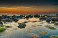 Colorful sunset over Baltic sea. Travel in Latvia - Baltic sea sunset on rock beach Royalty Free Stock Image