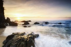 Travel and leisure concept, beautiful sea view scenery over stunning sunrise background. Sunlight beam and soft wave hitting beach rocks Stock Images