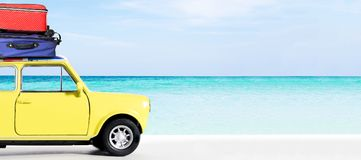 Travel and Leisure trip in the summer. Vintage yellow car on the seaside beach with travel bags on the roof. Travel and Leisure trip in the summer royalty free stock images