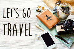 Travel. let`s go travel text sign concept . summer travel wander. Lust. map camera sunglasses passport money phone hat shells car on white wooden background top Stock Photos