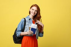 Travel and Lifestyle concept: Full length studio portrait of pretty young student woman holding passport with tickets stock photography