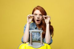 Travel and Lifestyle Concept: Portrait of a shocked girl in denim dress with suitcase looking at camera over. Golden yellow background royalty free stock photos
