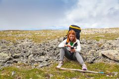 Travel Lifestyle and survival concept rear view. Hiking woman with backpack sits on the rocks and verifies the route on the navigator on the mountains on a stock images