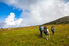 Travel Lifestyle and survival concept rear view. Two hiking women and men with backpack go along the path to the mountains in a long hike on a warm summer day royalty free stock photos