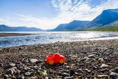 Travel of little red car. Little red toy car on coast of Lama lake Putorana plateau, Russia beyond of Arctic circle Stock Images