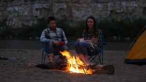 Travel and love concept. Young lovely couple near fireplace on camp stock footage