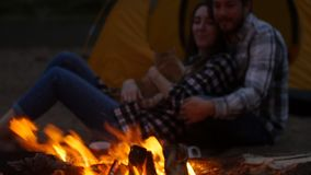 Travel and love concept. Young lovely couple near fireplace on camp stock video