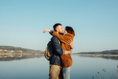 Travel and love. Happy young couple walking along the shore of blue lake in hipster clothes. Beautiful young couple in hipster clothes hugging in the background royalty free stock photography