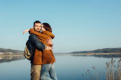 Travel and love. Happy young couple walking along the shore of blue lake in hipster clothes. Beautiful young couple in hipster clothes hugging in the background royalty free stock photo