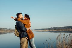 Travel and love. Happy young couple walking along the shore of blue lake in hipster clothes. Beautiful young couple in hipster clothes hugging in the background royalty free stock image