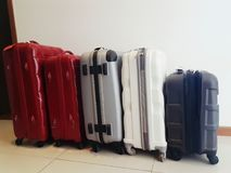Travel luggages of different sizes, shapes, make and colours sta. Cked in a row on floor Stock Images