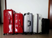 Travel luggages of different sizes, shapes, make and colours sta. Cked in a row on floor Stock Image
