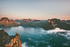 Travel man alone on the edge cliff in mountains above fjord royalty free stock image