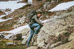 Travel Man with backpack climbing mountains. Lifestyle survival concept adventure outdoor active vacations mountaineering sport wild nature Stock Image