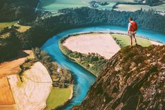 Travel Man on mountains cliff edge. With backpack Adventure lifestyle concept active weekend summer vacations river aerial view Stock Photo