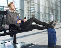 Travel man relaxing at airport with cellphone Royalty Free Stock Image
