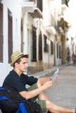 Travel man sitting on sidewalk reading map Stock Images