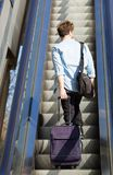 Travel man standing on escalator with bags Stock Images