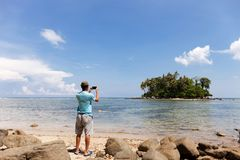 Travel man standing take a photo with smartphone small island in stock photo