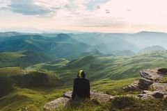 Travel man tourist sitting alone on the edge mountains over green valley adventure lifestyle extreme vacations green landscape. Travel man tourist sitting alone stock photo