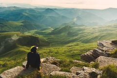 Travel man tourist sitting alone on the edge mountains over green valley adventure lifestyle extreme vacations green landscape. Travel man tourist sitting alone stock photos