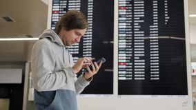Travel man using smartphone at airport. Young caucasian traveler checking boarding time with mobile phone app in. Terminal or train station stock video
