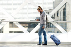 Travel man walking and looking at mobile phone Stock Photography