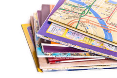 Travel maps. Pile of world maps across white royalty free stock photos