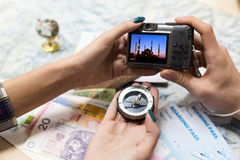 Travel Memories and Dreams Mood Composition. Young Couple scrolling images on portable Camera from recent Journey topographic Map Compass foreign Cash Notes and Royalty Free Stock Photo