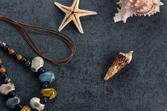 Travel Memories. Starfish, screw shell and necklace on grayish ground Stock Image
