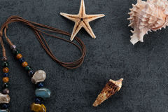 Travel Memories. Starfish, screw shell and necklace on grayish ground Royalty Free Stock Images