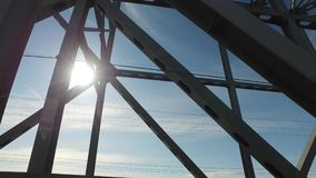 Travel on the metal bridge. Metal structures flashed against the sky. On the blue sky the sun shines brightly. The bridge held electric power transmission line stock video