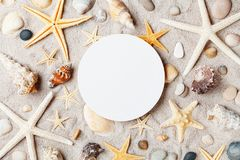 Travel mockup from starfish and seashell on sandy beach with paper blank. Stock Photo