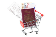 Travel money in shopping trolley cart. Passport, flight boarding pass and Euro notes in a supermarket shopping trolley cart - studio shot with a white background Royalty Free Stock Photos