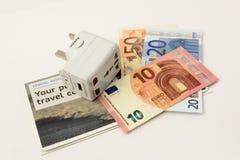 Travel money and travel plug. International travel plug and Euro notes isolated on a white background royalty free stock photos