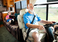 Travel by Motor Home. Retired senior couple traveling by motor home.  The husband drives while the wife reads in back Royalty Free Stock Photos