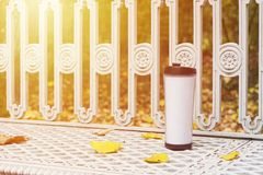 Travel mug with coffee. Stays on white bench among yellow fall leaves Royalty Free Stock Image