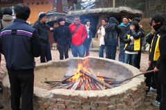 Travel in Naminara republic, Korea. NAMINARA REPUBLIC, KOREA - NOVEMBER 26 : The unidentified group of tourists are standing around fireplace on November 26 royalty free stock image